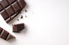 La barra de chocolate quebrada salió de la visión superior aislada posición Fotografía de archivo