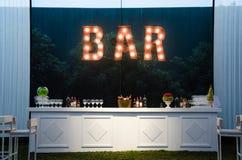 La barra es una muestra abierta, la barra de madera pintada blanca para una boda, el concepto de decoración Imágenes de archivo libres de regalías