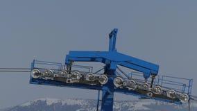 La barre bleue de la station d'ascenseur de chaise sur le fonctionnement de station de sports d'hiver et l'isolat de rotation banque de vidéos