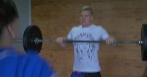 La barre d'haltérophilie de gymnase de forme physique de Crossfit par la femme et l'homme groupent la séance d'entraînement Barre clips vidéos