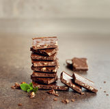 La barre de chocolat au lait avec des écrous a décoré les feuilles en bon état vertes sur une surface brune Photo stock