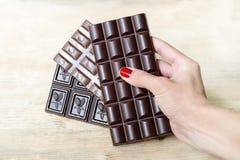 La barre du chocolat de lait, noir et poreux dans une main du ` s de femme aiment une fan Ton chaud, fond en bois Images stock