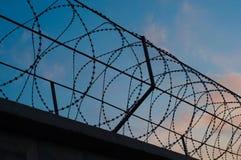 La barrière avec le barbelé a étiré des cercles sur le fond du Th Photos libres de droits