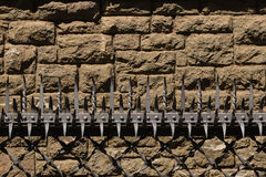 La barrière avec les fourches et le solide de sécurité a lapidé le mur Images libres de droits