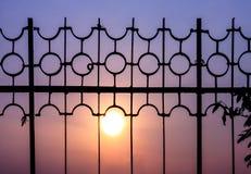La barrière crée une silhouette gentille au temps de coucher du soleil Photo libre de droits