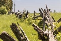 La barrière de rail fendue de cèdre courbe par des champs à la communauté rurale à une ferme Image libre de droits