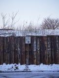 La barrière en bois avec une manière signent dedans la neige photos stock