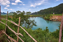 La barrière en bois avec une turquoise a coloré la rivière près de la ville de Phong Nha en parc national de coup de Phong Nha KE Images stock