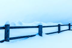 La barrière ou la haie et les tas de la neige dans la campagne ou dans le village pendant le jour d'hiver froid image stock