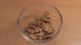 La base de nueces se vierte en el plato de cristal Cámara lenta metrajes