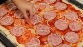 La base de pizza Cuisson de pizza mettez la tomate dans la pizza arrangez les ingrédients dans la pizza petite main du ` s d'enfa banque de vidéos