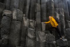La base de roche près de la plage noire de sable Photographie stock