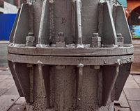 La base de un nuevo pilar manchado del metal con los pernos Imagen de archivo libre de regalías