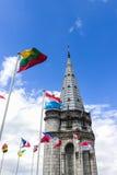 La basilica della nostra signora del rosario e delle bandiere dei paesi differenti contro il cielo blu Lourdes, Francia, Hautes Fotografie Stock