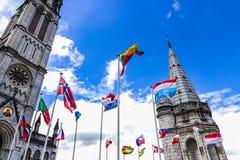 La basilica della nostra signora del rosario e delle bandiere dei paesi differenti contro il cielo blu Lourdes, Francia, Hautes Immagini Stock