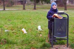 La basura y el tiro de la selección de la sonrisa del niño a dejar en desorden pueden Imagenes de archivo