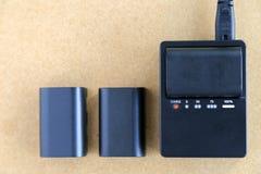 La batería de la cámara está cargando en cargador de batería en la tabla de madera Foto de archivo libre de regalías
