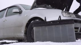 La batería de coche descargada en el fondo del coche en el invierno, el conductor camina cerca del coche, el comenzar de los prob metrajes
