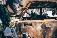 La battaglia di paintball, giocatori combatte intorno all'automobile bruciata fotografia stock libera da diritti