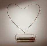 La batteria ed il cavo hanno fatto la forma del cuore Immagine Stock