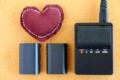 La batterie d'appareil-photo charge sur le chargeur de batterie d'un pillo de coeur Photographie stock libre de droits