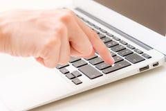 La battitura a macchina del dito entra su un computer portatile Fotografia Stock