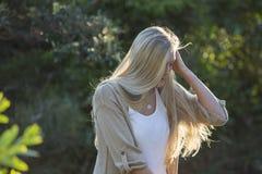 La beauté australienne avec de longs cheveux blonds regarde vers le bas avec Sun coulant par des cheveux Photographie stock libre de droits