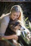 La beauté australienne avec de longs cheveux blonds se repose avec son chien de colley Photos stock
