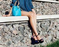 La beauté aux jambes longues se repose sur les étapes en pierre un jour chaud d'été dans un équipement de denim, des chaussures à Photographie stock libre de droits