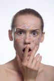 La beauté créative avec géométrique composent sur une femme Lignes blanches et taches grises d'argile sur un beau jeune visage im Image stock