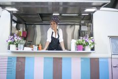 La beauté et la jeune femme travaille dans un camion de nourriture photo stock