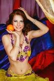 La beauté orientale tient une orange images stock