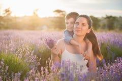 La beaux mère et enfant heureux sur la lavande mettent en place au coucher du soleil Photo stock