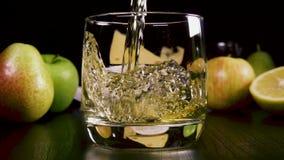 La bebida alcohólica fuerte de la cámara lenta vierte en un vidrio cerca del bocado metrajes