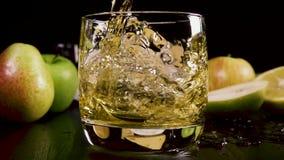 La bebida alcohólica fuerte de la cámara lenta vierte en un vidrio cerca del bocado almacen de metraje de vídeo