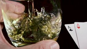 La bebida alcohólica fuerte de la cámara lenta vierte en un vidrio y naipes almacen de video