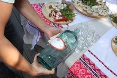 La bebida alcohólica nacional ucraniana del ` s de la gente - moonshine el licor y vodka y los bocados, canapes Imagenes de archivo