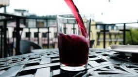 La bebida carbónica de la cereza se vierte en un vidrio de una botella, cámara lenta metrajes