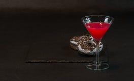 La bebida cosmopolita un vidrio de martini adornó con dos que lo hace el oreo Fotos de archivo