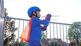 La bebida de enfriamiento, niño en traje del super héroe con la botella plástica en brazos bebe el agua mineral al aire libre almacen de metraje de vídeo