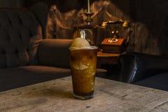 La bebida fría de Frappe sirvió en una tabla en la noche en una sala de estar con la decoración del vintage fotografía de archivo libre de regalías