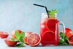 La bebida o el jugo anaranjada de la limonada del verano adornó las hojas de menta en el tarro de cristal en fondo de la turquesa Fotografía de archivo
