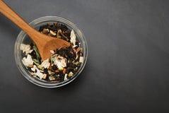 La bebida sana del té herbario de Acaccia en cuenco y el tamiz sobre fondo negro copian el espacio Bebida sana, frialdad fotos de archivo libres de regalías