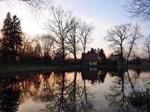 La bei casa ed alberi si avvicinano al lago nella sera, Lituania Fotografie Stock