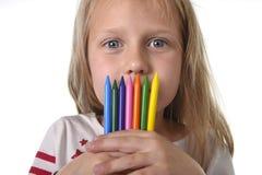 La bella bambina che tiene i pastelli multicolori ha messo nel concetto di istruzione dei bambini della scuola di arte Fotografia Stock Libera da Diritti