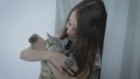 La bella bambina comunica delicatamente con il vostro gatto amato alla finestra stock footage