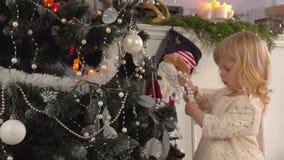 La bella bambina decora un albero di Natale video d archivio
