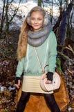 La bella bambina dolce si è vestita in un cappotto e negli stivali di pelle di pecora che si siedono sul tronco e nei precedenti Immagini Stock