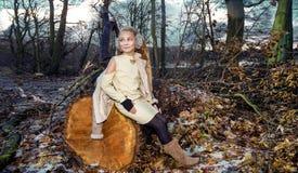 La bella bambina dolce si è vestita in un cappotto e negli stivali di pelle di pecora che si siedono sul tronco e nei precedenti Fotografia Stock Libera da Diritti