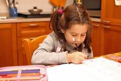 La bella bambina scrive con la matita sull'esercizio della scuola del libro Fotografia Stock
